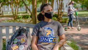 Student wearing face covering sitting on bench on campus