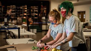 Two students wearing masks chopping vegetables at Spartan Open Pantry
